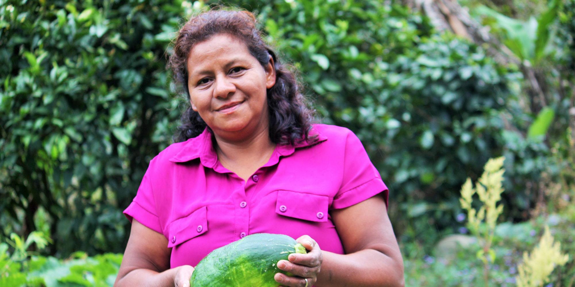 En kvinna iklädd cerise blus poserar med en pumpa i händerna framför en odling.