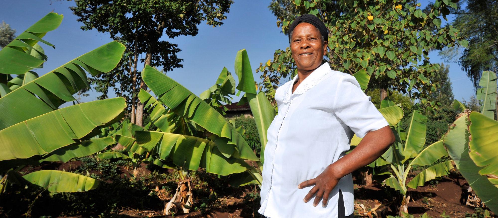 Mercy Njoki Gathiongo poserar framför en bananodling, leende.