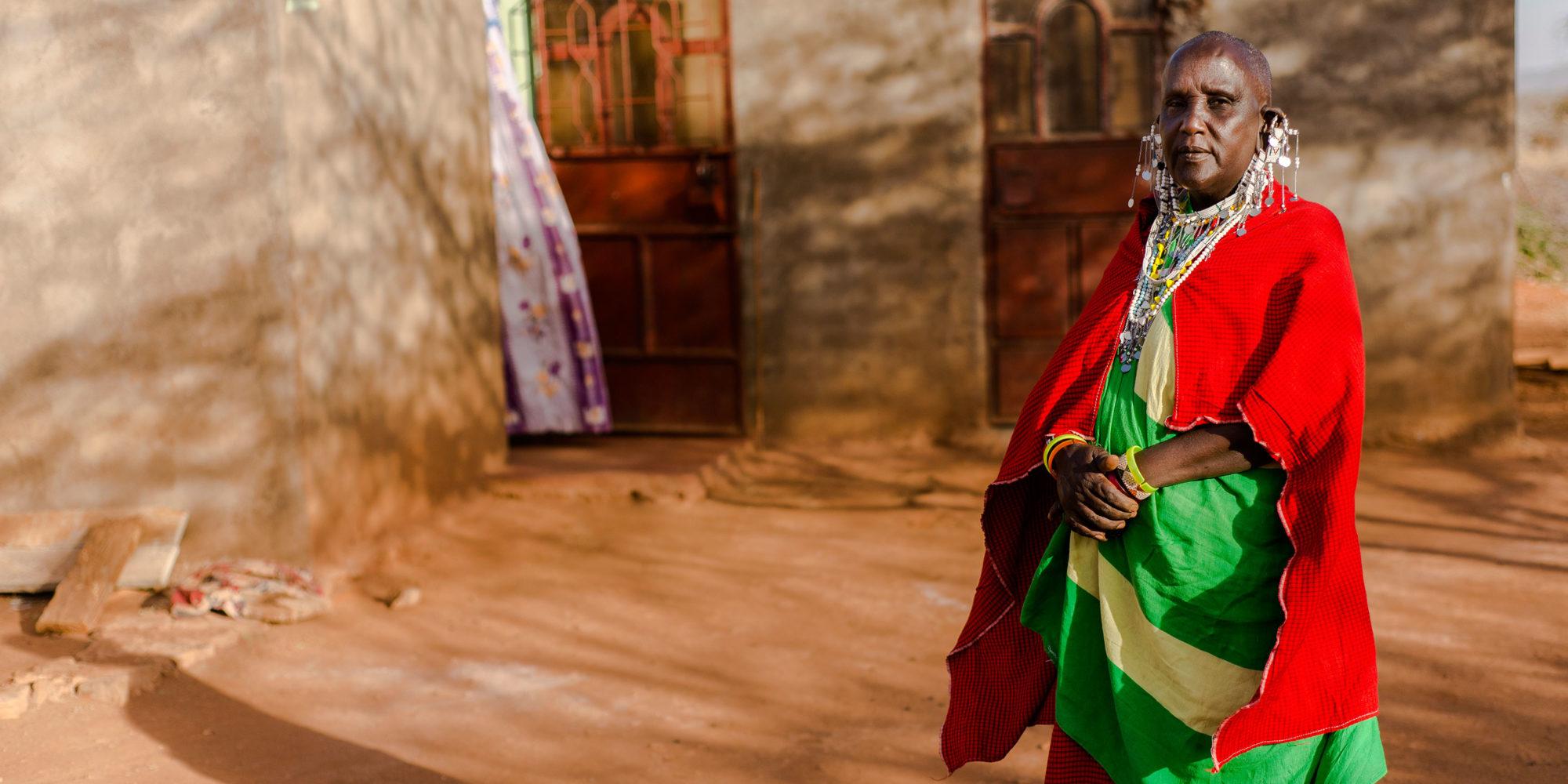 En massajkvinna iklädd traditionell dräkt i rött och grönt poserar framför ett hus i rödbrunt tegel.