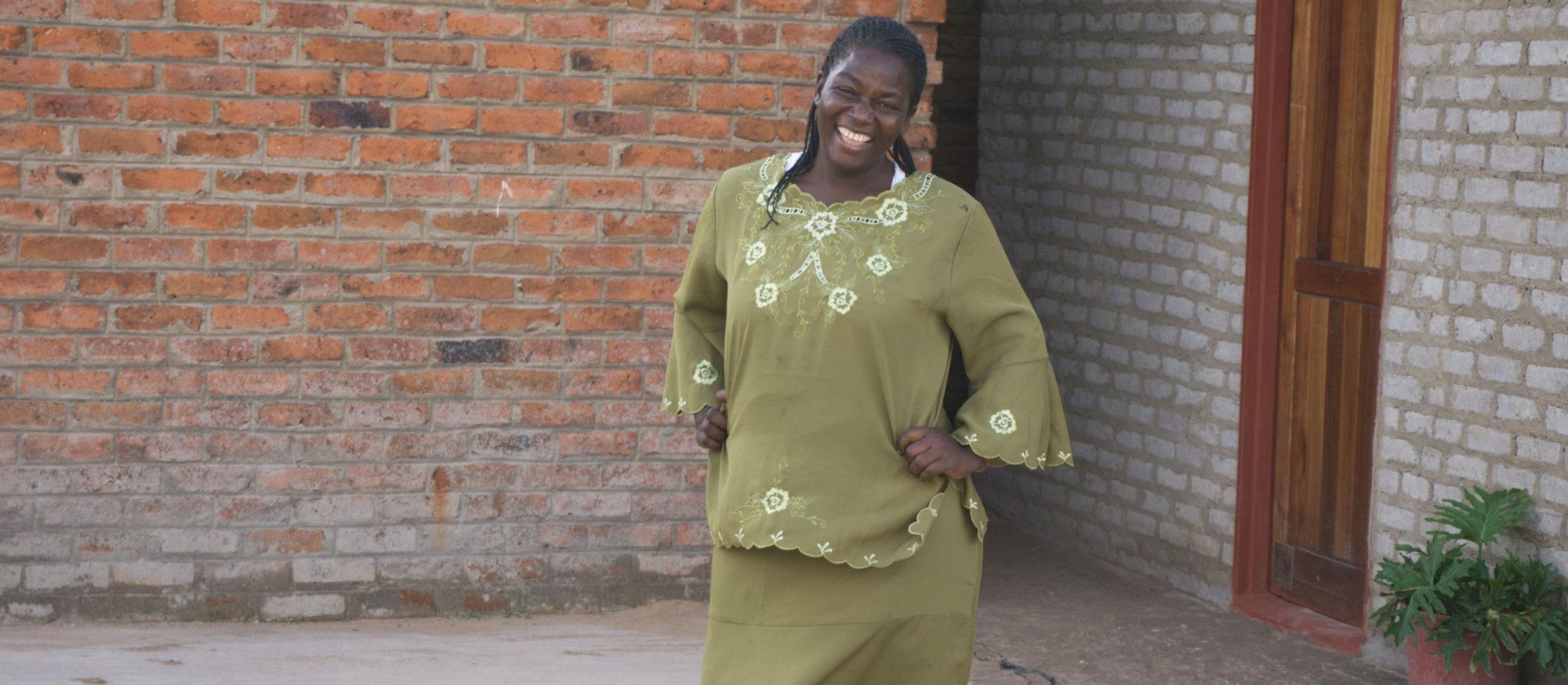Rachel Bvunzawabaya poserar leende utanför sitt hus,