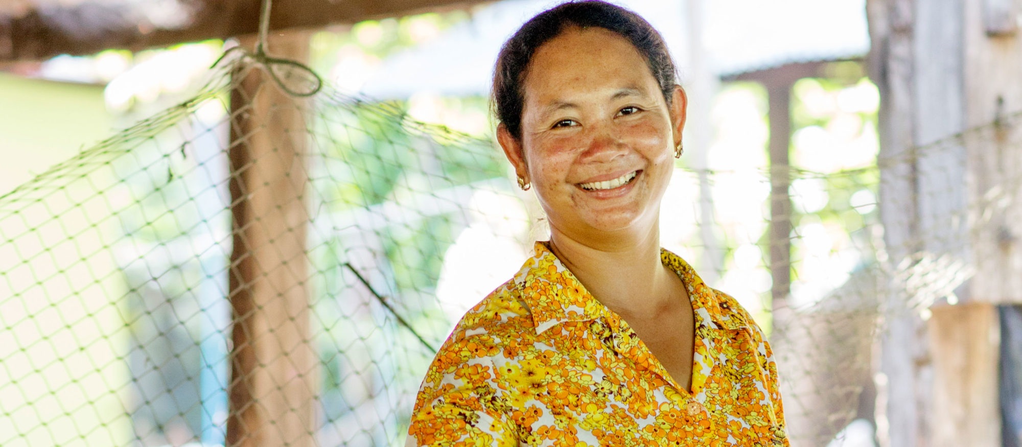 En leende kvinna iklädd gult tittar in i kameran