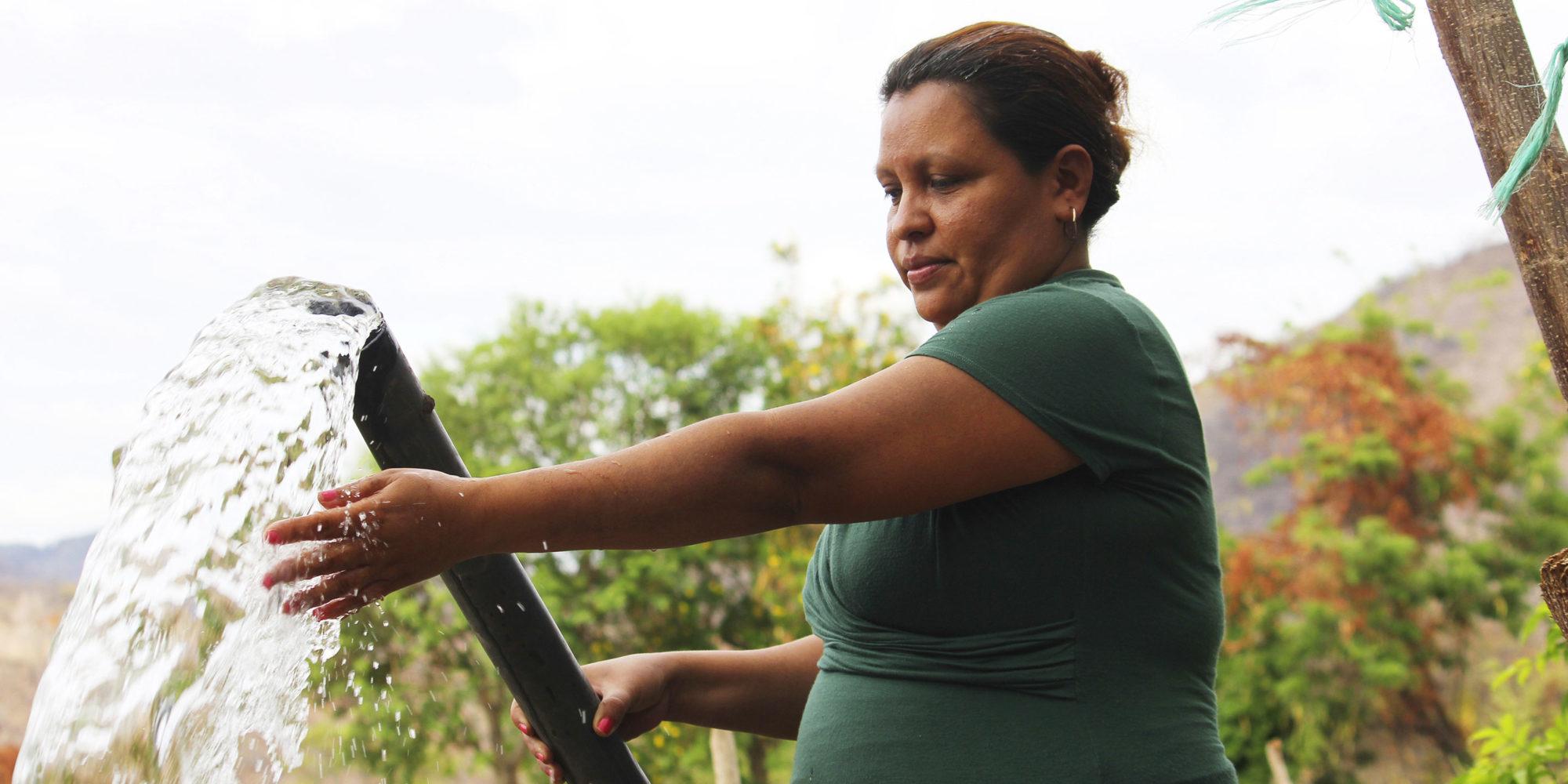 En kvinna står och pumpar vatten från en brunn.