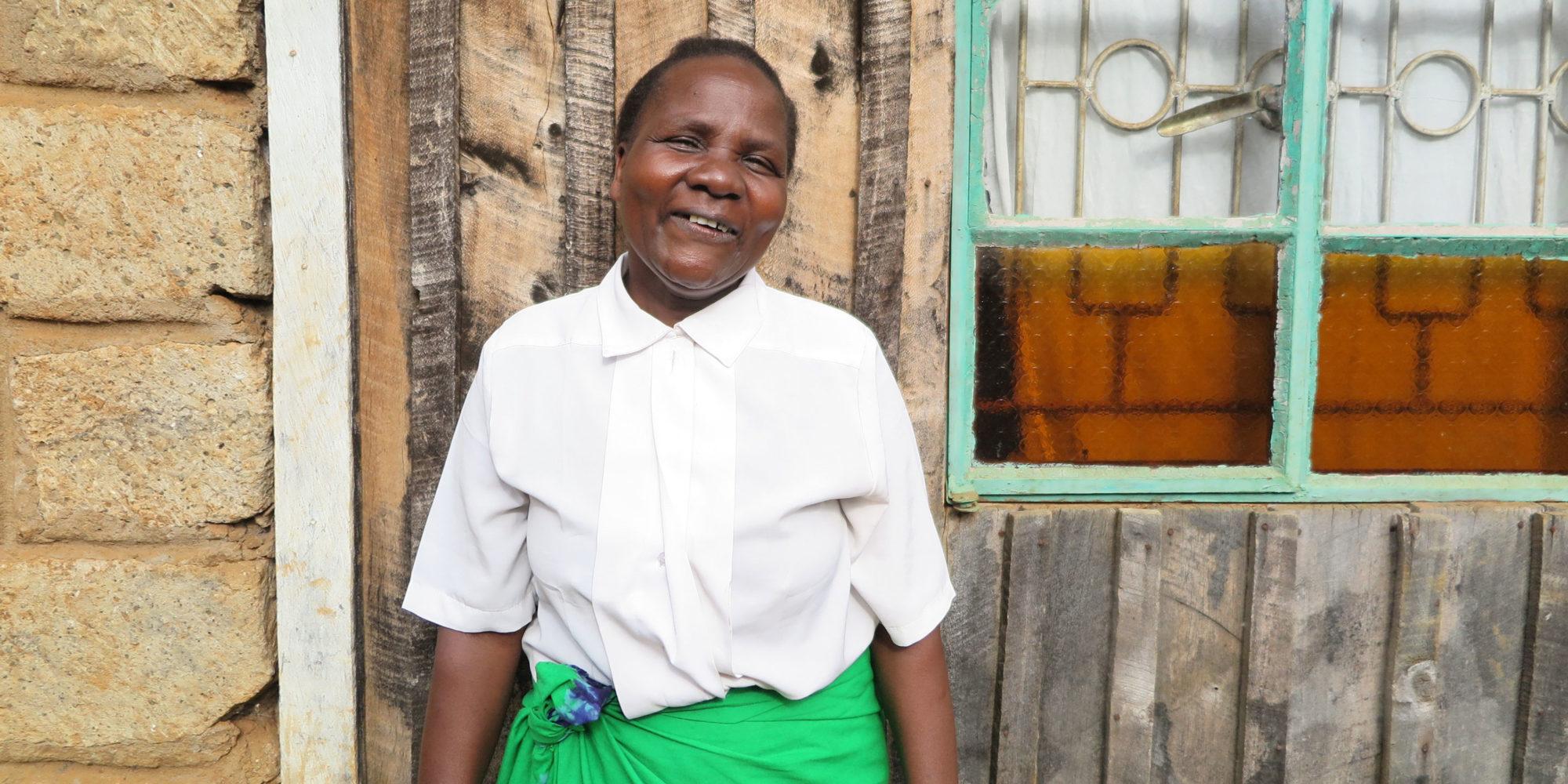 En äldre kvinna poserar leende framför sitt hus