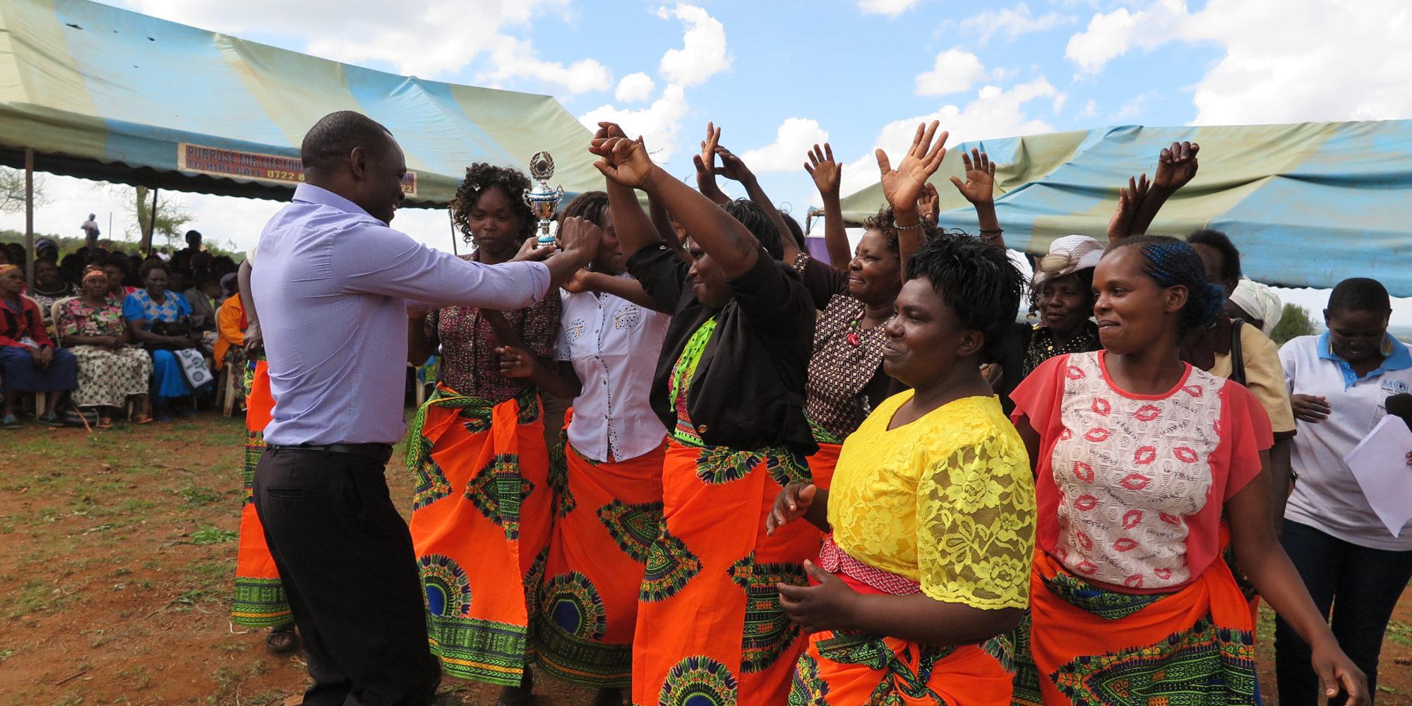 En grupp kvinnor jublar när de tar emot en pokal .