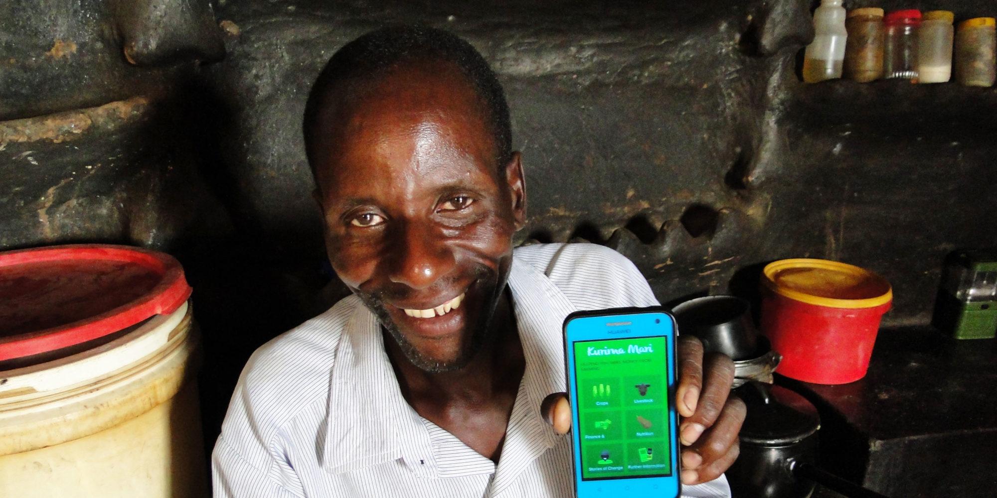 En man håller upp en mobilskärm med en app.
