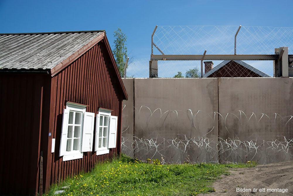 En mur går precis bredvid ett rött hus och delar en stad i två delar.