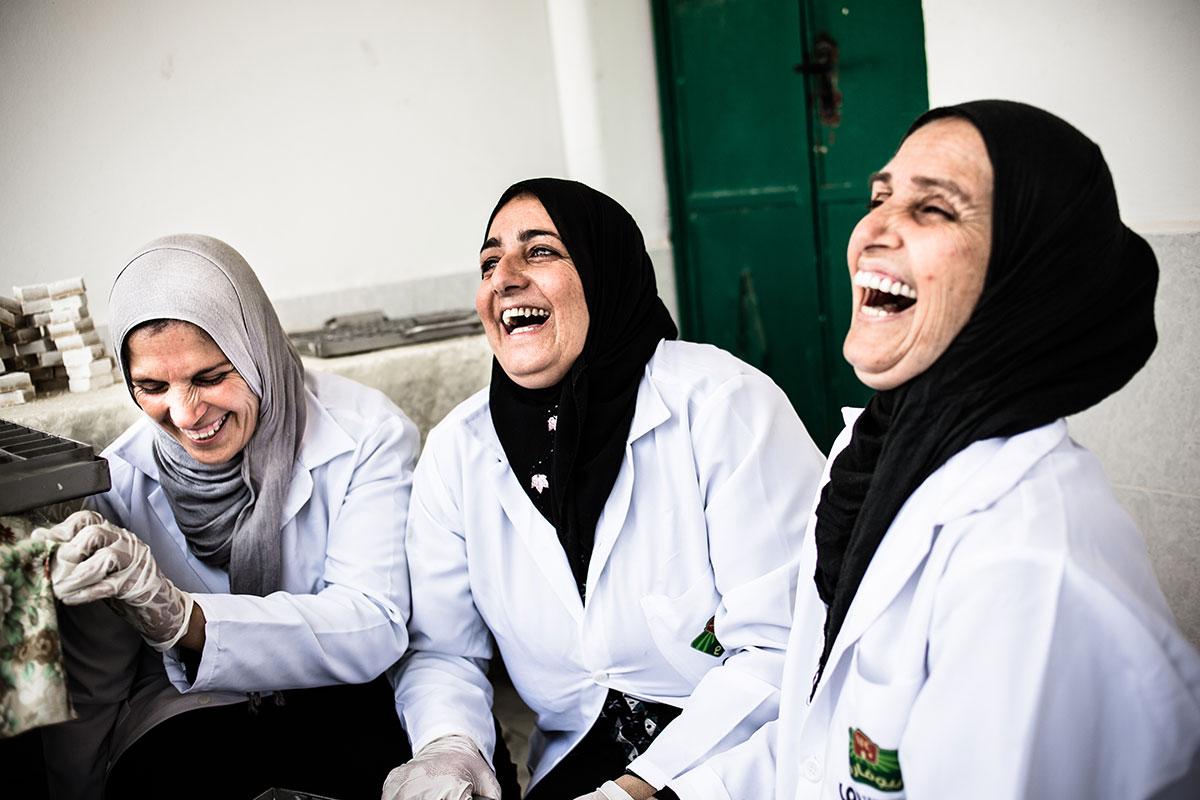 Skrattande kvinnor i vita rockar tar en paus i arbetet.