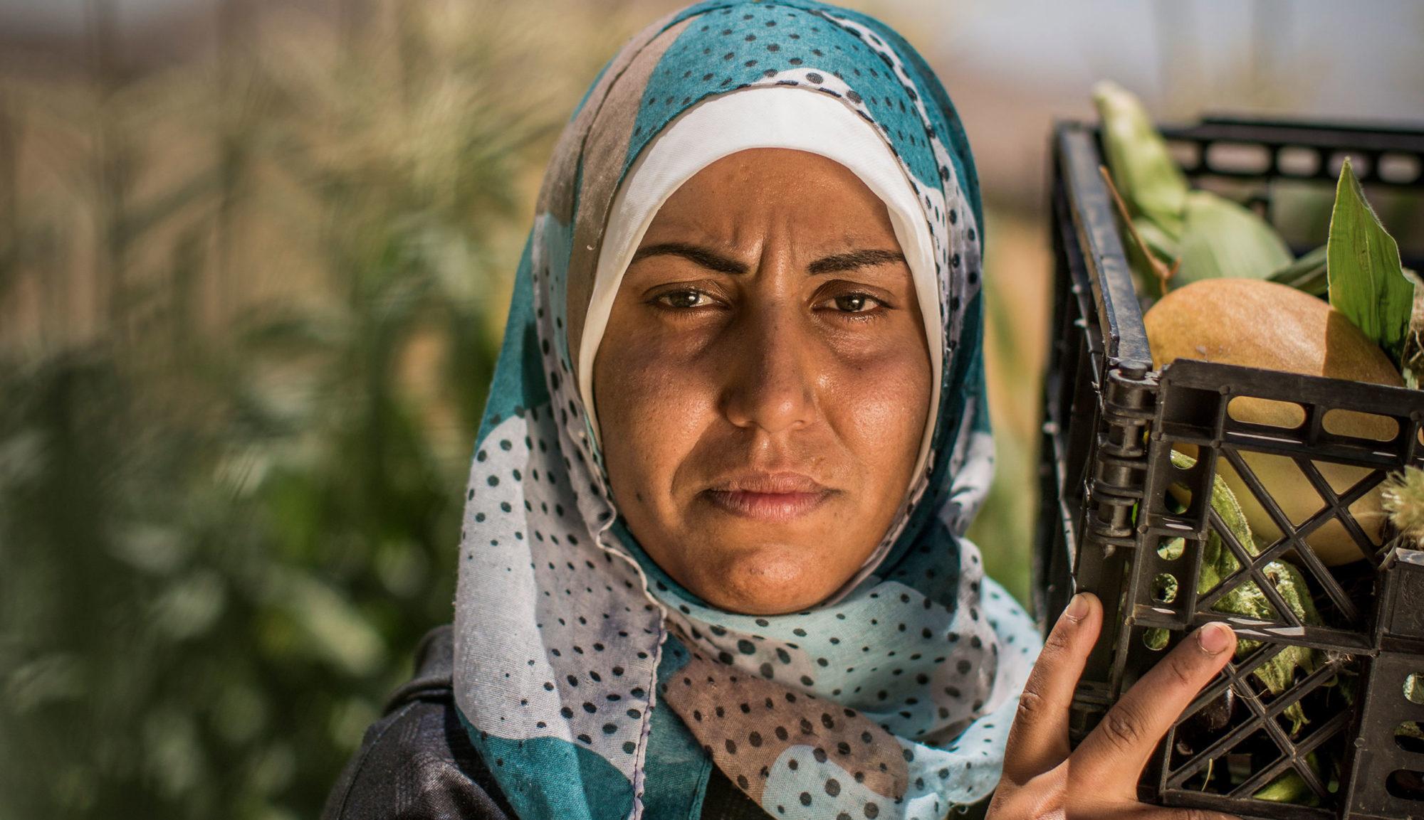 Närbild på en palestinsk kvinna som med allvarlig blick tittar in i kameran. På axeln bär hon en grönsaker.