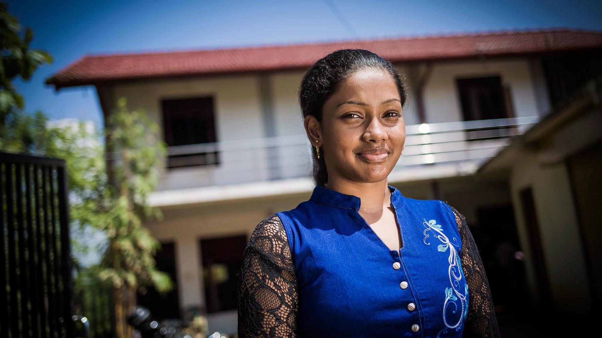 Eng unge kvinna i blått tittar leende in i kameran.