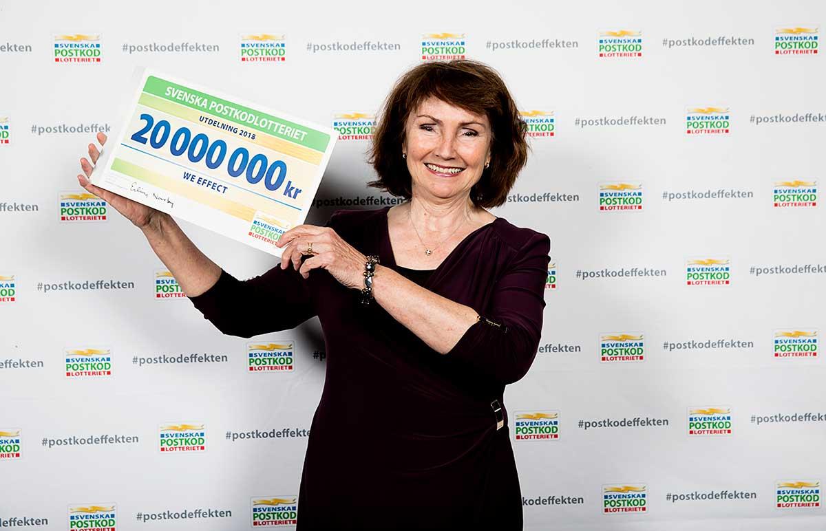 Anneli Rogeman håller upp en stor check med beloppet 20 miljoner.