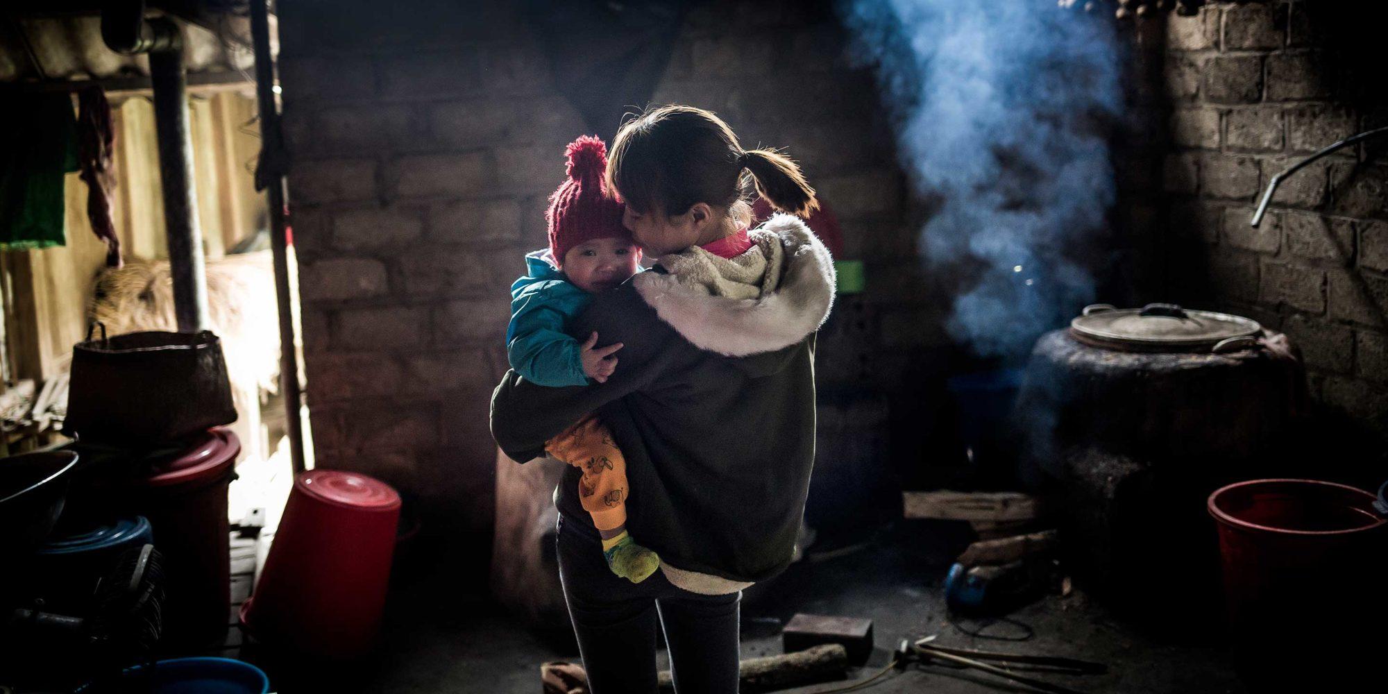 En ung kvinna håller ett litet barn i famnen. Hon står inne i ett mörkt, rökigt hus.