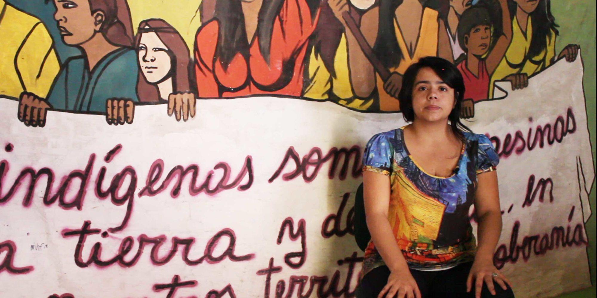 En ung kvinna sitter framför en banderoll.